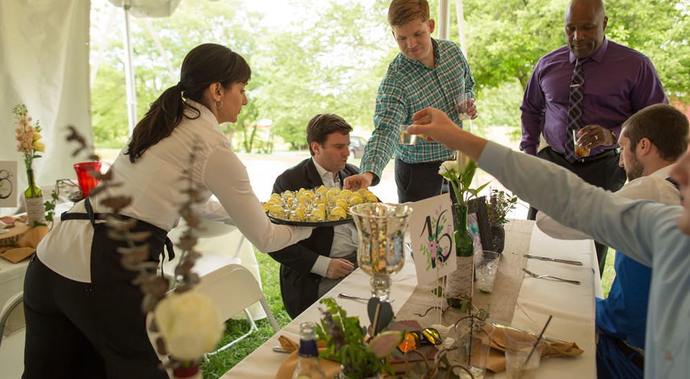 Farm to Table Wedding Passing around Lemon Drops to guests